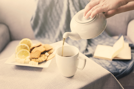 Woman pouring tea in mug from kettle Stock Photo