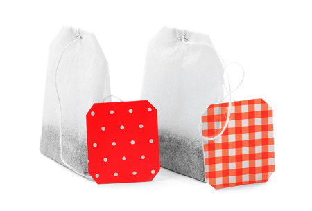 Unused teabags with red labels isolated on white background