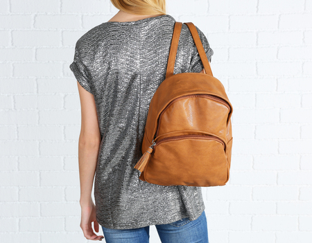 Back of woman with brown leather backpack against white brick wall background Stockfoto