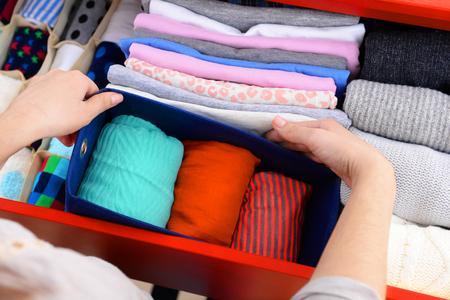 Vestiti pieganti della donna nel primo piano della cassettiera