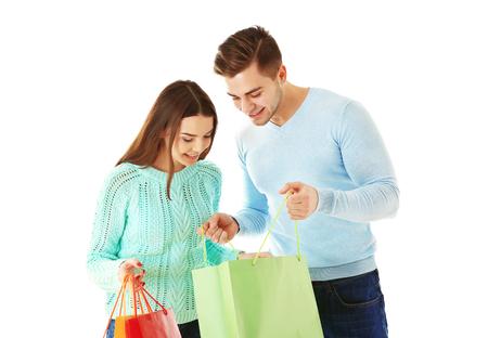 Junges Paar mit bunten Einkaufstaschen lokalisiert auf Weiß