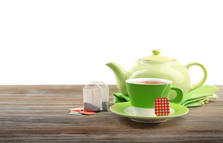 Cup of tea with tea bags and teapot on wooden background against grey background Stock Photo