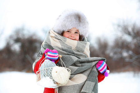 Little girl holding basket with skeins in snowy park outdoor Stockfoto
