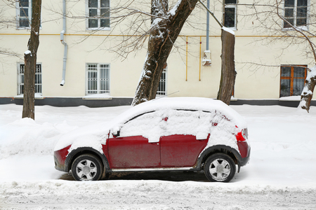 Car covered with snow beside building Stock Photo