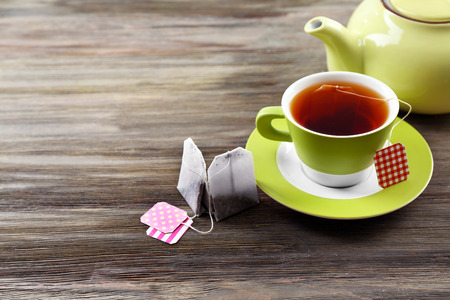Cup of tea with tea bags and teapot on wooden table background