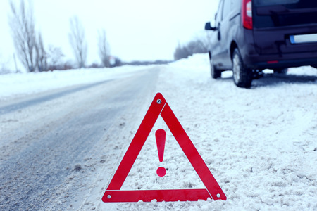 Car breakdown with red triangle on snowy winter road, outdoor