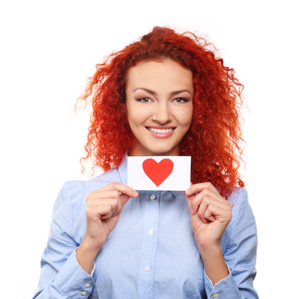 Red-haired young woman holding paper red heart, isolated on white Stock Photo