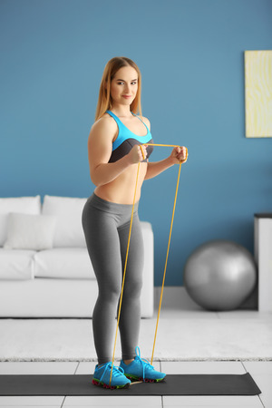 Young sportswoman doing exercises with rubber band on a mat at home