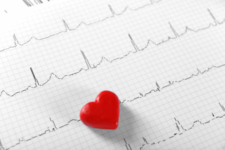 Cardiogram chart with small red heart on table closeup
