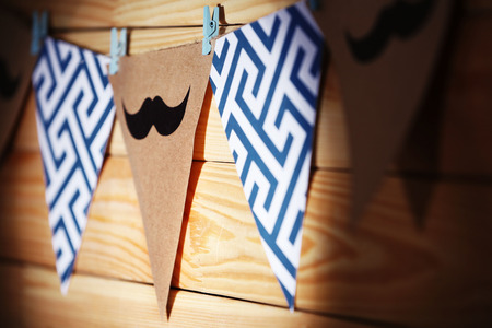 Hanging flags with mustaches on wooden background