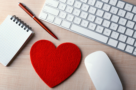 Computer peripherals with red heart, pen and notebook on light wooden table