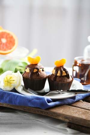 Two tasty cupcakes with slice of mandarin and chocolate on a plate over light wooden background
