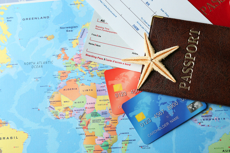 Credit cards with passports and tickets for vacations on the world map background Foto de archivo