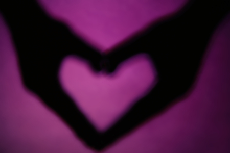 Hand shaped heart on purple background