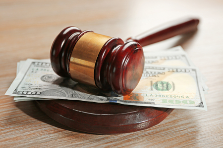 Law gavel with dollars on wooden table background, closeup