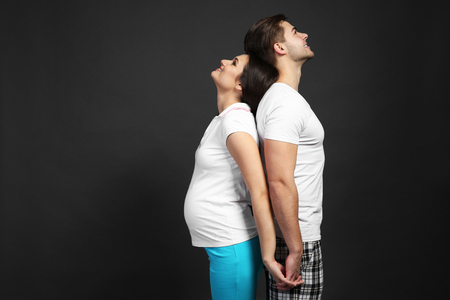 Young pregnant woman with husband on dark background