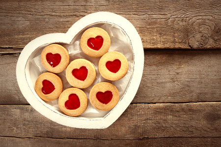 Assortment of love cookies in box on wooden background, closeup