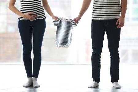 Pregnant woman with husband holding childs clothes in front of the window Stock Photo