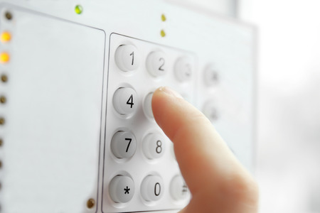 Security alarm keypad with male hand, closeup Foto de archivo