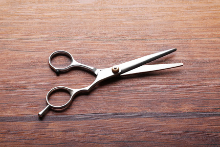 Professional metal scissors lying on the wooden table, close up Stock Photo