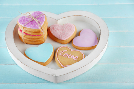 Assortment of love cookies in box on blue background, closeup 写真素材