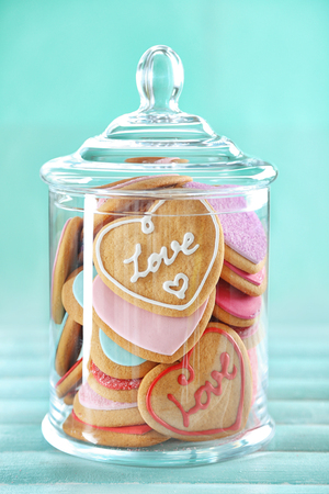 Surtido de galletas de amor en tarro sobre fondo azul. Foto de archivo