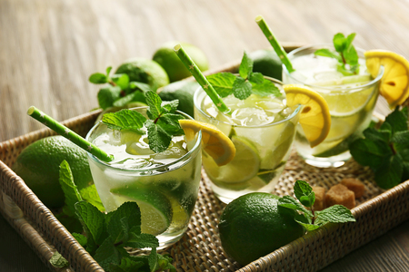 Mojito drink with lime, lemon and mint on wooden table Foto de archivo