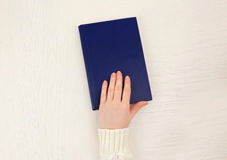 Female hand holding a blue book cover  on white desk, top view