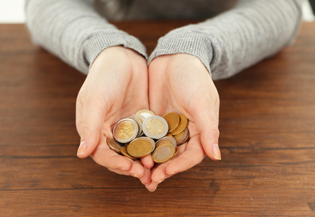 Young woman in a grey shirt  holding a heap of coins in her hands above  wooden table, close up Stock Photo