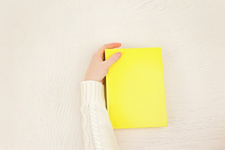 Female hand holding a yellow book cover  on white desk, top view