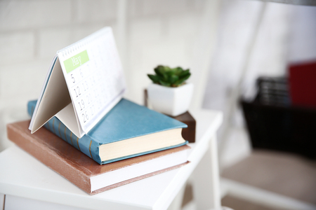Loose leaf calendar and two books on white stool, close up