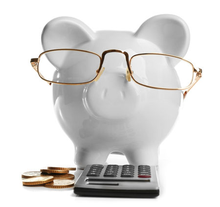 Pink piggy bank with coins, glasses and calculator, isolated on white