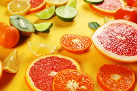 Set of sliced citrus fruit on yellow background