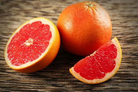 Juicy grapefruits on stripped napkin, close up Фото со стока