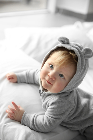 Little baby boy in grey pajamas lying on the bed at home
