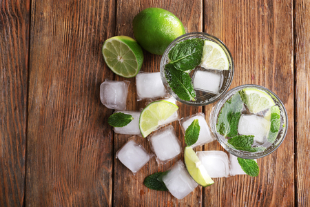 Fresh cocktails with mint, ice and lime on wooden table background