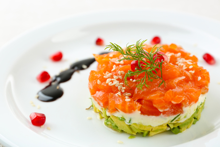 Fresh tartar with salmon, avocado and soy sauce on white plate, close up