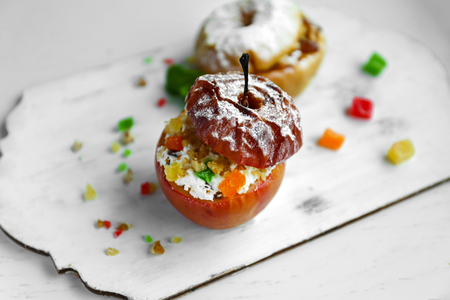 Baked apple with cottage cheese, raisins, candied fruit and nuts on white wooden tray