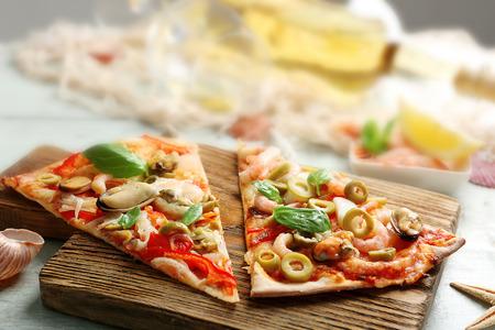 Tranches de pizza aux fruits de mer, poivrons rouges, olives vertes et bouteille de vin sur table en bois
