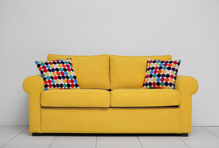 Yellow sofa with multicoloured pillows on white wall background Stock Photo