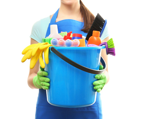Young woman holding cleaning tools and products in bucket, isolated on white