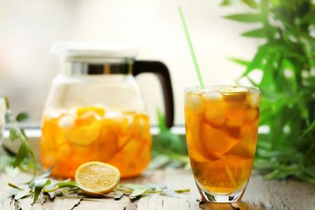 Glass and jar of iced tea with lemon on a windowsill Stock Photo