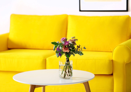 Jar of roses on the table beside yellow sofa Stock fotó