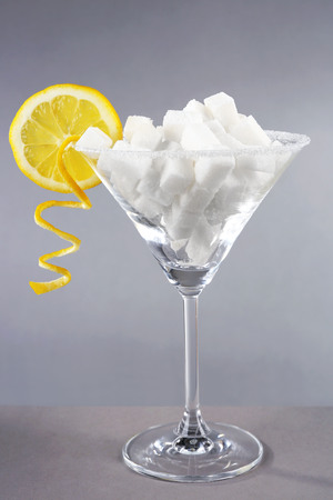 Cocktail glass full of sugar with fruit on grey background