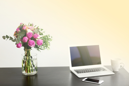 Jar of roses on table beside laptop