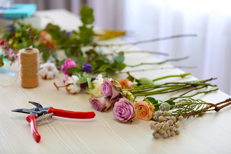 Roses and gardening scissors on table in the room