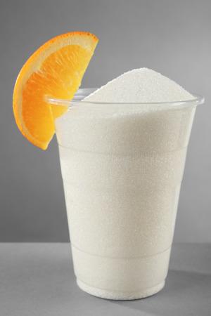 Plastic glass full of sugar with orange on grey background