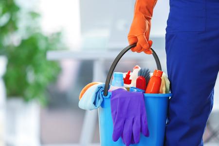 sosteniendo productos de limpieza y herramientas en la cuchara, cerrar Foto de archivo
