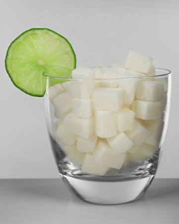 Glass full of sugar with lime on grey background