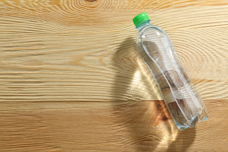 Bottle of water on the wooden table, top view
